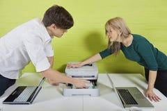 Sidosikt av unga businesspeople som ställer in - upp skrivaren med bärbara datorer på skrivbordet Royaltyfri Foto