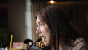 Sidosikt av unga flickan i svarta handskar som äter en hamburgare i kafé stock video