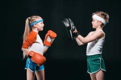 Sidosikt av ungar som låtsar boxning som isoleras på svart Arkivfoto