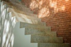 Sidosikt av vit tom trappa med brun bakgrund för tegelstenvägg royaltyfria bilder