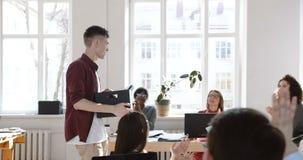 Sidosikt, lycklig le ung affärsman som skriver in det moderna kontoret med en ask som hurras och välkomnas av kollegor arkivfilmer