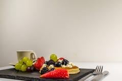 Sidosikt på den stora pannkakan med piskad kräm- och ny frukt, s Arkivbild