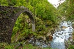 Sidosikt på det Ponte Romano Intragna Bridge nederlaget i vallen arkivbilder