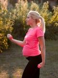 Sidosikt på gravid kvinna med hantlar Arkivfoton