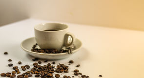 Sidosikt på svart kaffe i en vit kopp på tefatet Royaltyfri Foto