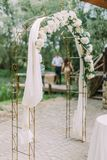 Sidosikten av bröllopbågen dekorerade med vita blommor Arkivfoto