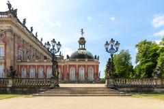 Sidosikten av Das Neue Palast, parkerar in Sanssouci, Potsdam, Tyskland med dess trappa som ingången, de falska järnlyktorna och  royaltyfri bild