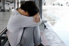 Sidosikten av den frustrerade utmattade unga asiatiska affärsmannen sitter och kramar hans knä upp till bröstkorgen arkivfoton