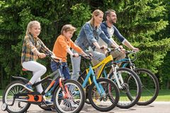 sidosikten av den lyckliga familjridningen cyklar, medan spendera tid tillsammans arkivfoto