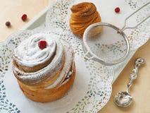Sidosikten av den moderna efterrätten dekorerade med sockerpulver Ny muffin eller cruffin arkivbilder