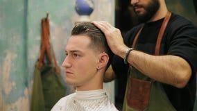 Sidosikten av den unga stiliga caucasian mannen med piercing i hans öra som får hans hår, klädde och utformade vid ett skäggigt stock video