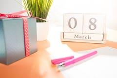 Sidosikten av det orange skrivbordet med koppen kaffe, gåvan, blommor och anteckningsboken Royaltyfri Fotografi