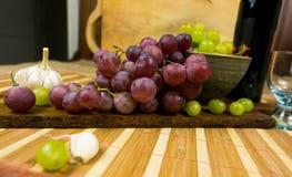 Sidosikten av en röd och gul muscat färgade druvan, flaskan av vin, vitlök och ett exponeringsglas på ett träbräde - stilleben arkivbild