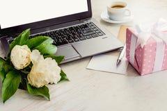 Sidosikten av ett däck med datoren, buketten av pionblommor, koppen kaffe, det tomma kortet och rosa färger prack gåvaasken Vit l arkivbild
