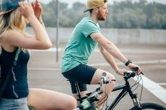 Sidosikten av ett ungt par på cirkulering rider i bygd fotografering för bildbyråer