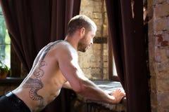 Sidosikten av mannen med tatoo på hans tillbaka göra skjuter ups Royaltyfri Bild