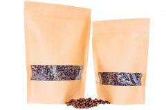 Sidosikten av pappers- doypack för två kraft står upp påsar med fönstret och blixtlåset som fylls med kaffebönor på vit bakgrund royaltyfria bilder