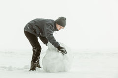 Sidosikten av pojken som rullar ett stort, kastar snöboll Royaltyfri Bild