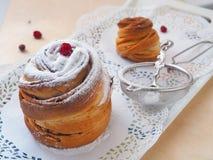 Sidosikten av två moderna efterrätter dekorerade med sockerpulver Ny muffin eller cruffin arkivbilder