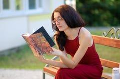 Sidosikten av unga flickan i Eyesglasses och långt rött klänningsammanträde på bänken i staden parkerar och läsa någon bok Arkivbild