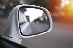 Sidospegel av en bil som reflekterar vägen och trädsikten bredvid royaltyfria bilder