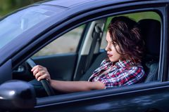 Sidostående av den unga kvinnan som kör en bil på hög hastighet Arkivfoton