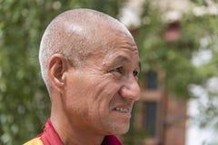 Sidostående av en gammal tibetan buddistisk munk Arkivbilder