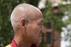 Sidostående av en gammal tibetan buddistisk munk Arkivbild