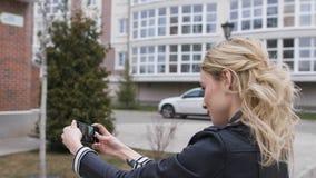 Sidostående av en härlig blond flicka som använder en smart telefon för att knyta kontakt som tar selfiesbilder i ett förorts- he lager videofilmer