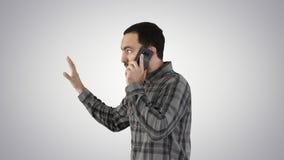 Sidostående av en lycklig student som går och talar på mobiltelefonen på lutningbakgrund arkivfilmer