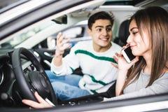 Sidostående av par i bil Man med skri och gest medan flicka som talar på telefonen i bil Royaltyfria Foton