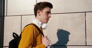 Sidoståenden av den attraktiva unga tonåringen i gul tröja promenerar gatan Han rymmer påsen och lager videofilmer