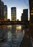 Sidovinkelsikten av den Chicago stadsnatten tänder upplyst och reflekterad på ett djupfrysta Chicago River Royaltyfri Foto