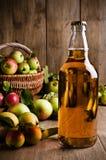Sidra en botella con las manzanas fotografía de archivo
