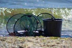 Sieć rybacka z ryba i wiadro stoimy na plaży zdjęcia stock