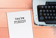Sie ` bezüglich abgefeuert auf Papier mit Schreibmaschine, Jobkrise und Büro sitzen lizenzfreie stockbilder