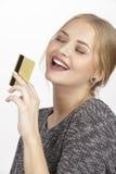 Sie gibt viel Geld durch goldene Kreditkarte aus Lizenzfreies Stockfoto