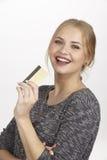 Sie gibt viel Geld durch goldene Kreditkarte aus Stockfoto