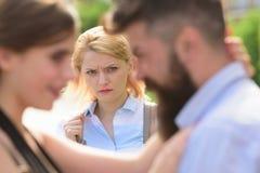 Sie ist offensichtlich eifersüchtig Bärtiger Mann, der seine Freundin mit einer anderen Frau betrügt Unglückliches Mädchengefühl  stockbilder