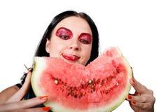 Sie leckt ihre Lippen, welche die Wassermelone betrachten Stockfoto