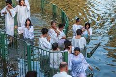 Sie leiten das Wasser ein, gekleidet in weiße Roben Stockbilder