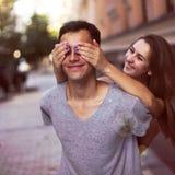 Sie schließt ihre Augen für einen Kerl, der sein Überraschungslächeln macht Lizenzfreie Stockbilder