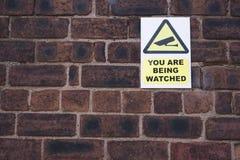 Sie sind aufgepaßtes CCTV-Symbolzeichen auf Backsteinmauer lizenzfreies stockfoto