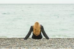 Sie sitzt zurück auf einem Pebble Beach durch Meer an einem bewölkten Tag, sein Kopf, der zurück geworfen wird Lizenzfreies Stockbild