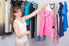 Sie wählte eine rosa Bluse vom Stapel von Kleidung Lizenzfreie Stockbilder