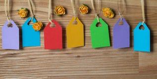 Sieben bunte Tags für Text und Papierblumen auf Holz. Lizenzfreie Stockbilder