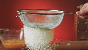 Sieben des Mehls durch Sieb, Zeitlupe 240fps Bäcker, der gemessenes Mehl auf einer Tabelle siebt Kochen und Zurückziehen stock video