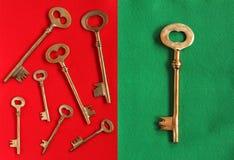 Sieben goldene Schlüssel in der unterschiedlichen Richtung auf das Rot geglaubt und einer groß Stockfotos