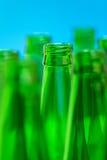 Sieben grüne Flaschenhälse auf blauem Hintergrund Stockfotos