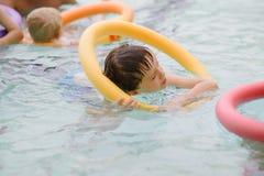 Sieben Jahre alte Junge, die lernen, am Pool zu schwimmen lizenzfreie stockfotografie